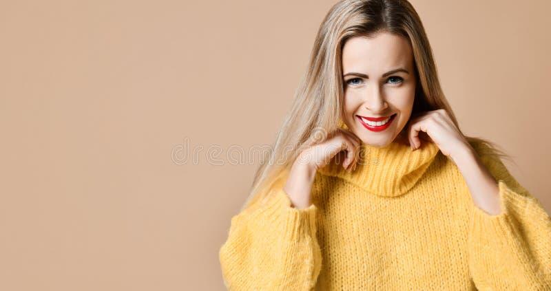 Glückliches Lächeln der jungen schönen Blondine in der großen gelben gestrickten Strickjackenbluse lizenzfreie stockfotografie