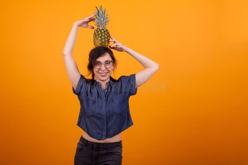 Glückliches Lächeln der jungen sexy Frau mit den Gläsern, die eine geschmackvolle Ananas auf ihrem Kopf im Studio über gelbem Hin lizenzfreie stockbilder