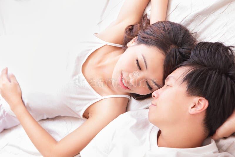 Glückliches Lächeln der Paare, das miteinander im Bett schaut stockfotografie