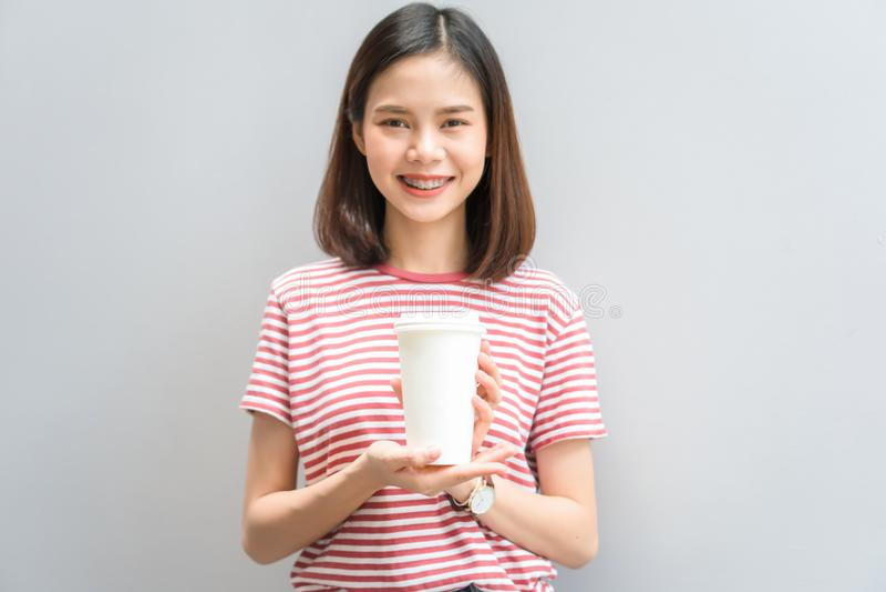 Glückliches Lächeln des jungen Mädchens und nett im roten Kleidergriff eine weiße Kaffeetasse in der Hand stockfotos