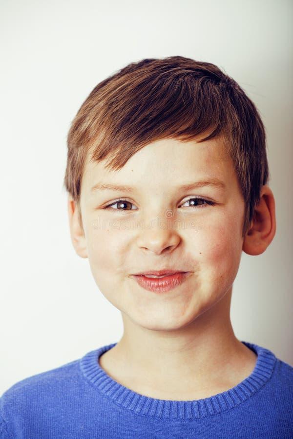Glückliches Lächeln des kleinen netten wirklichen Jungen lokalisiert auf weißem Hintergrund, Lebensstilleutekonzept stockfoto