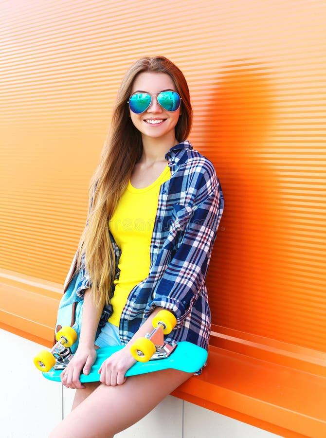 Glückliches lächeln recht blondes Mädchen, das Sonnenbrille mit dem Skateboard tragend hat Spaß ist stockbilder