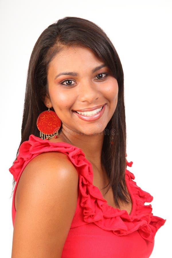 Glückliches Lächeln vom schönen Latinomädchen in der roten Oberseite lizenzfreie stockfotografie