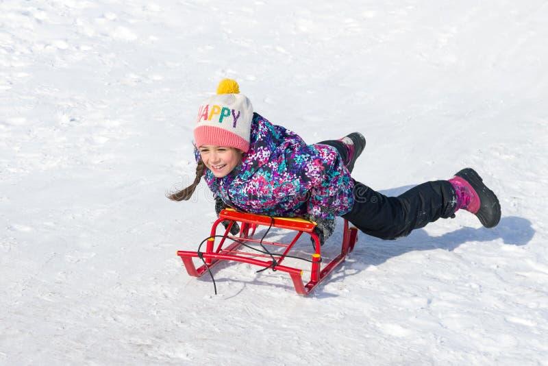 Glückliches lächeln wenig Mädchen auf einem Schlitten, der hinunter einen Hügel auf Schnee schiebt lizenzfreie stockbilder
