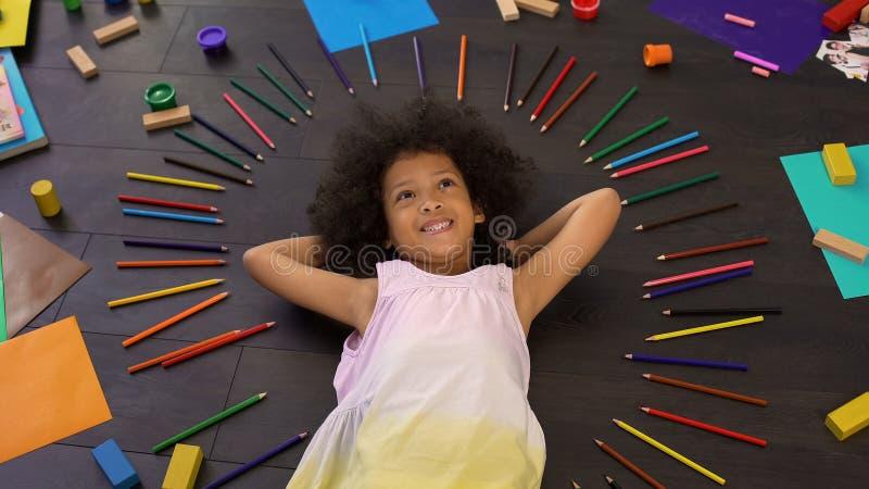Glückliches lächelndes afrikanisches weibliches Kind, das auf Boden liegt und über Feiertag träumt lizenzfreies stockbild