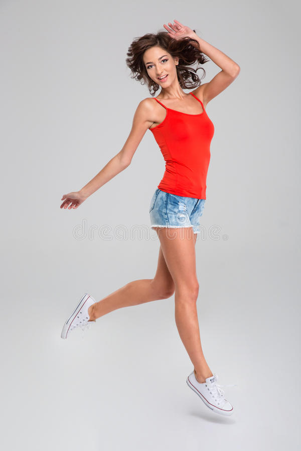 Glückliches lächelndes angesporntes Mädchen im Sprung lizenzfreie stockfotografie