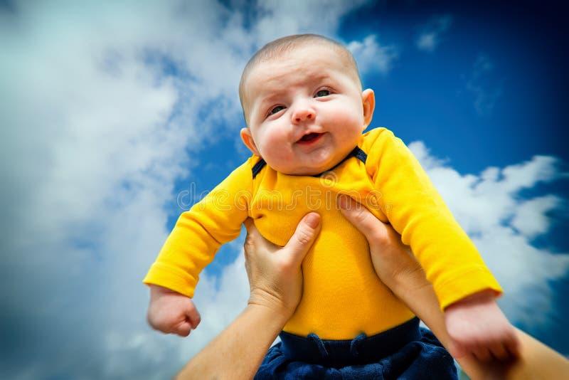 Glückliches, lächelndes Baby, das in die Luft angehoben wird lizenzfreies stockfoto