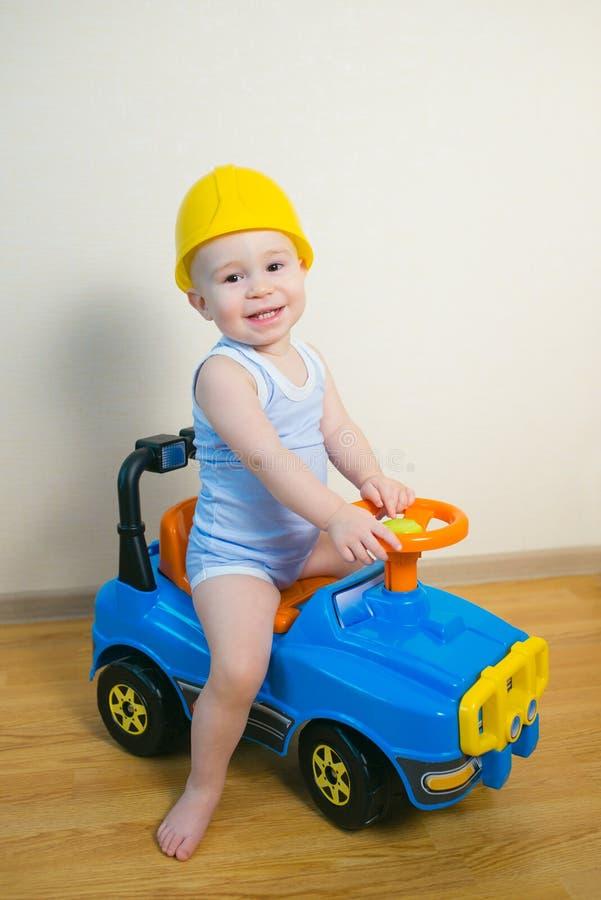 Glückliches lächelndes Baby, das zu Hause ein Spielzeugauto fährt stockbild