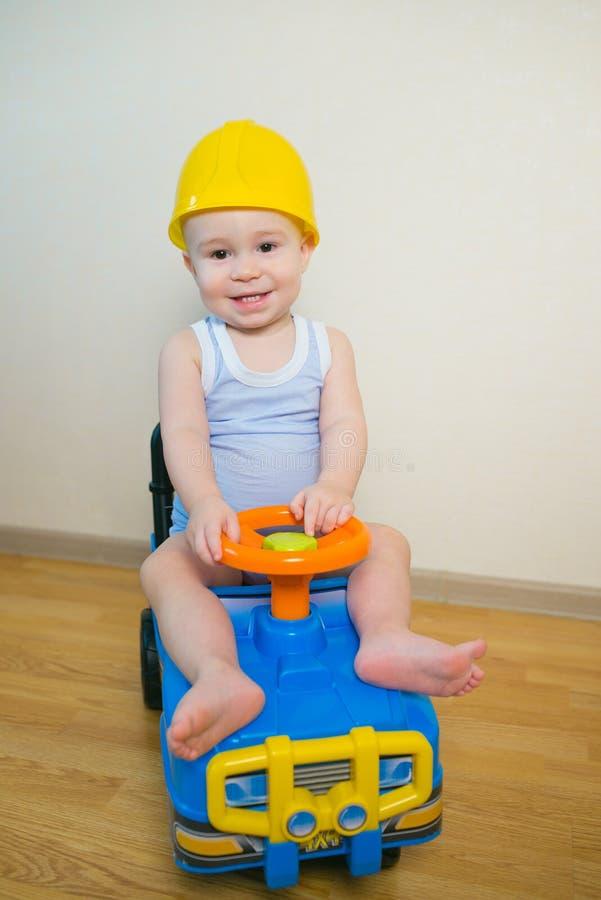 Glückliches lächelndes Baby, das zu Hause ein Spielzeugauto fährt stockbilder
