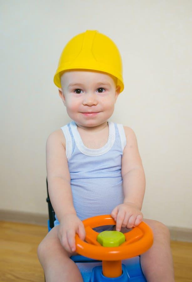 Glückliches lächelndes Baby, das zu Hause ein Spielzeugauto fährt stockfotos