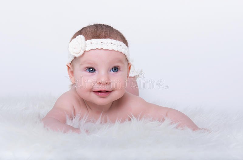 Glückliches lächelndes Baby mit blauen Augen stockfoto