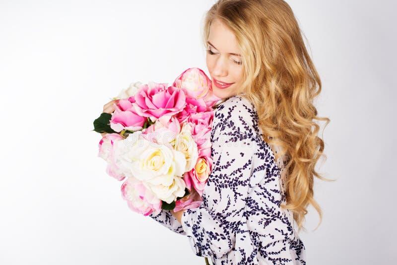 Glückliches lächelndes blondes Mädchen mit Blumenstrauß von Rosen lizenzfreie stockfotografie