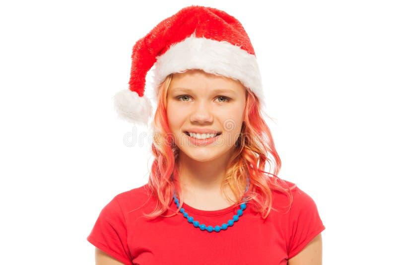 Glückliches lächelndes blondes Mädchen in Santa Christmas-Hut stockfotos