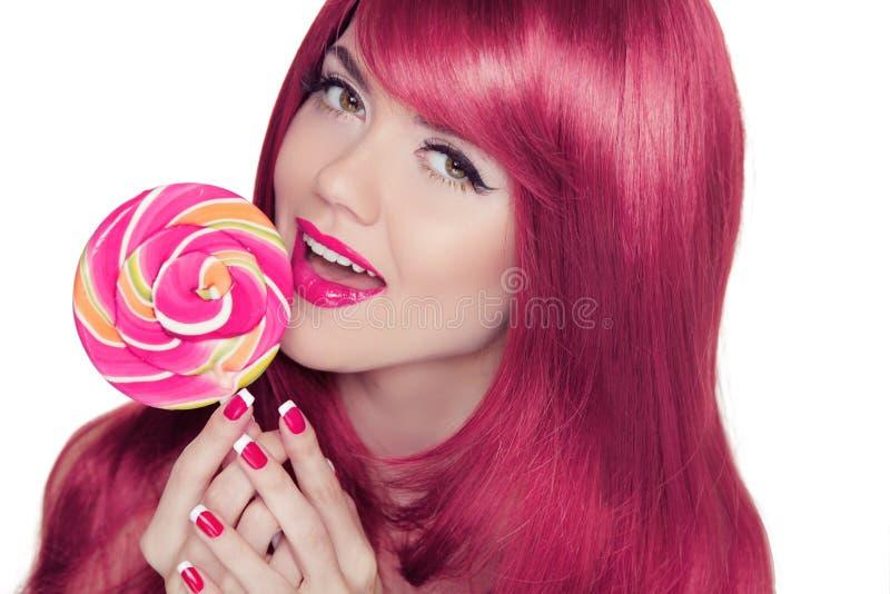 Glückliches lächelndes jugendlich Mädchen, das mehrfarbigen Lutscher mit Rosa hält stockbild