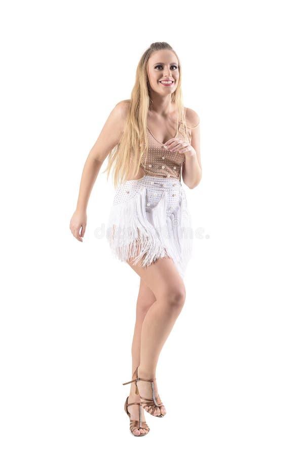Glückliches lächelndes junges Berufsfrauentanzen im cremefarbenen Kleid, das Kamera betrachtet lizenzfreies stockbild
