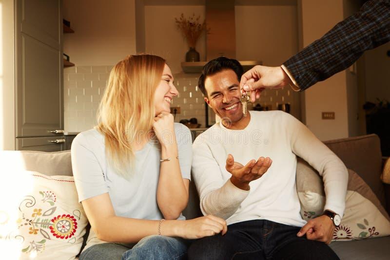 Glückliches lächelndes junges Paardarstellen Schlüssel ihres neuen Hauses lizenzfreie stockfotos