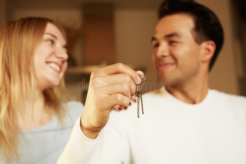 Glückliches lächelndes junges Paardarstellen Schlüssel ihres neuen Hauses stockfotos