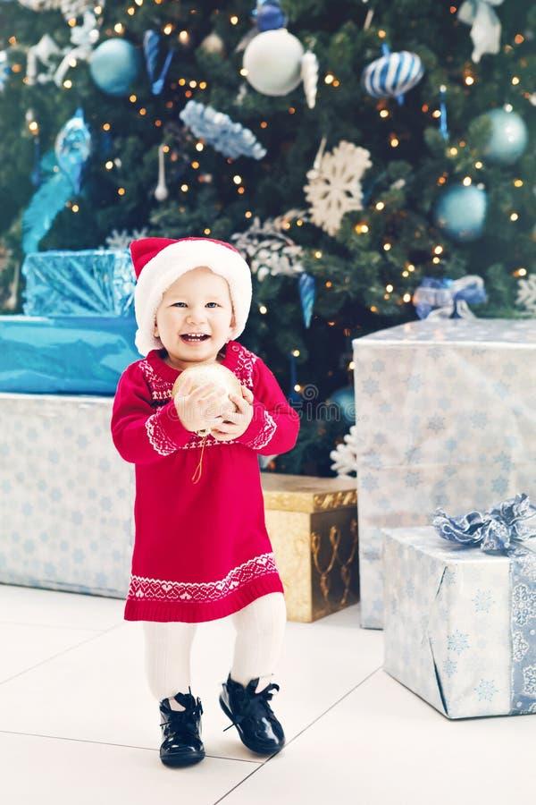 glückliches lächelndes kaukasisches Babykleinkind mit blauen Augen im roten Kleid und in Santa Claus-Hut, die Baum des neuen Jahr stockfotografie