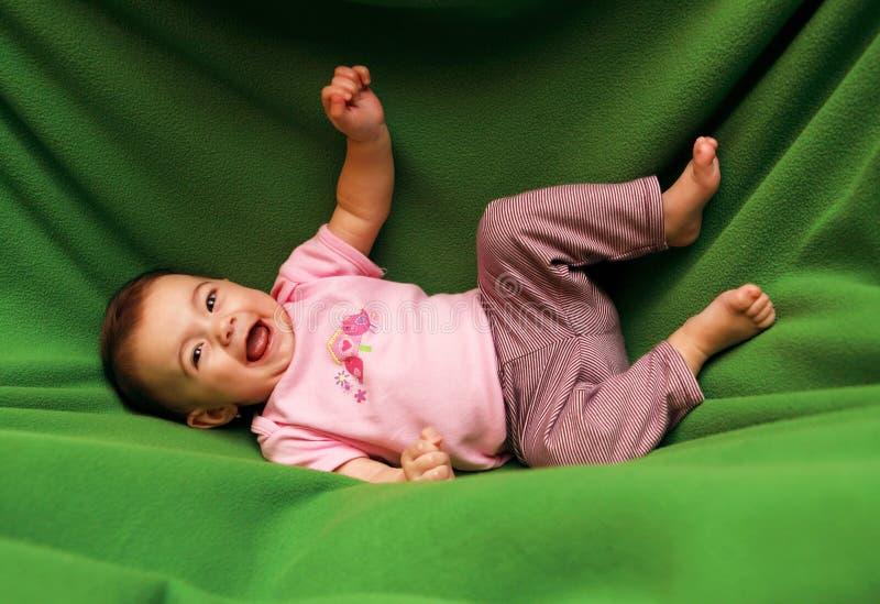 Glückliches lächelndes Kind auf Decke stockbild
