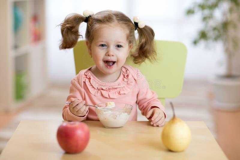 Glückliches lächelndes Kind, das Hafermehl mit Früchten isst Das Konzept des gesunden Frühstücks für Kinder stockfotos