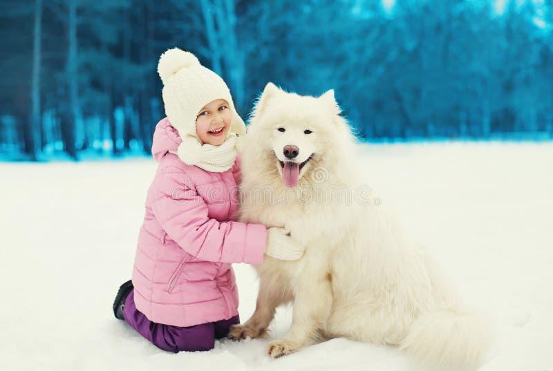 Glückliches lächelndes Kind, das mit weißem Samoyedhund auf Schnee im Winter spielt lizenzfreie stockfotos