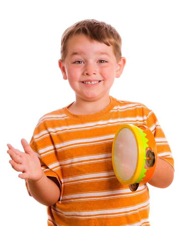 Glückliches lächelndes Kind, das Tambourine spielt stockfotografie