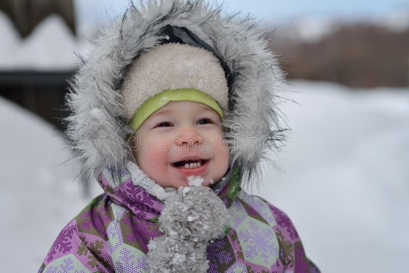 Glückliches lächelndes Kind, das am Wintertag geht lizenzfreies stockfoto