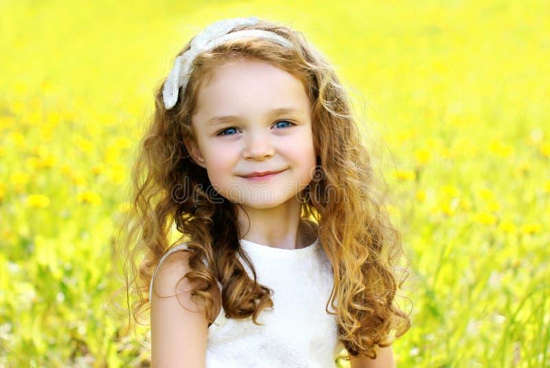 Glückliches lächelndes Kind des kleinen Mädchens des Porträts draußen im sonnigen Sommer stockfoto