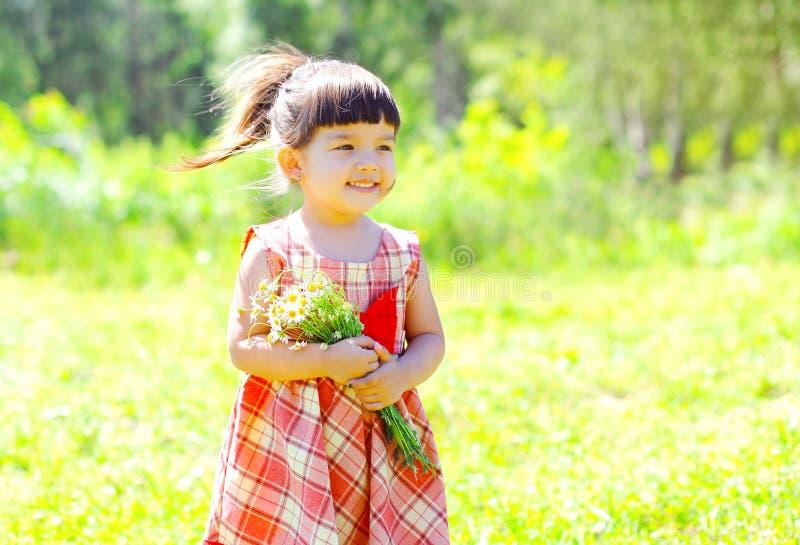 Glückliches lächelndes Kind des kleinen Mädchens des Porträts mit Blumen im Sommer lizenzfreies stockfoto