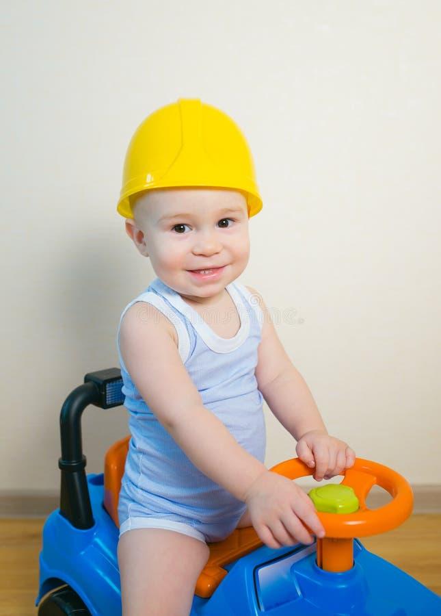 Glückliches lächelndes Kind im gelben Sturzhelm, der ein Spielzeugauto fährt stockfoto