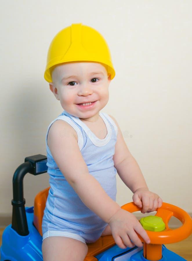 Glückliches lächelndes Kind im gelben Sturzhelm, der ein Spielzeugauto fährt lizenzfreies stockfoto