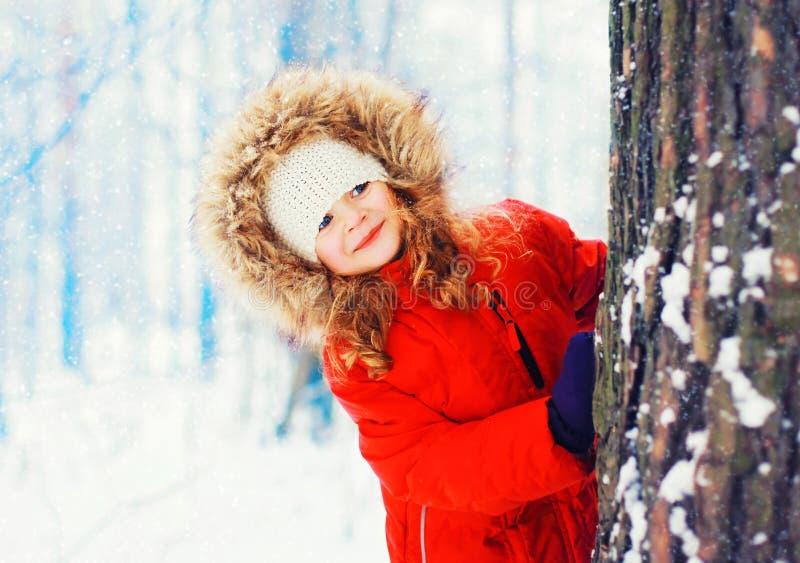 Glückliches lächelndes kleines Kind des Winterporträts, das nahe Baum spielt lizenzfreies stockfoto