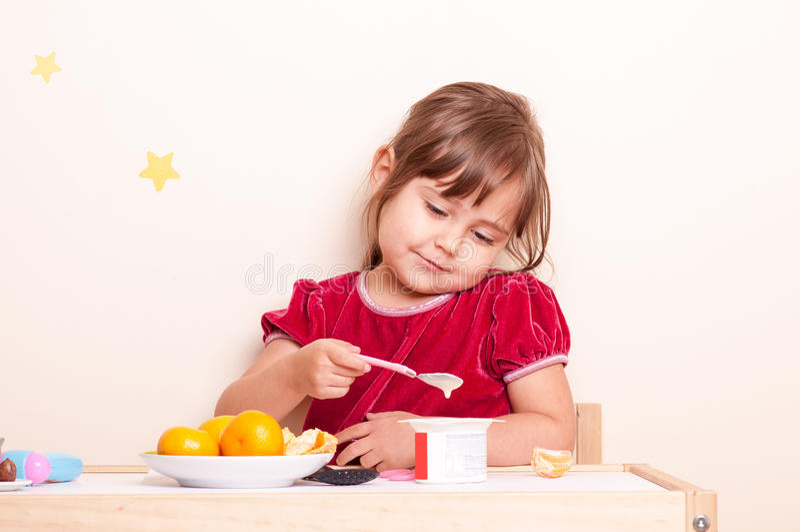 Glückliches lächelndes kleines Mädchen, das Früchte und Jogurt isst lizenzfreie stockfotos