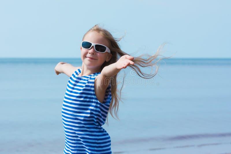 Glückliches lächelndes kleines Mädchen in der Sonnenbrille auf Strandferien stockfotografie