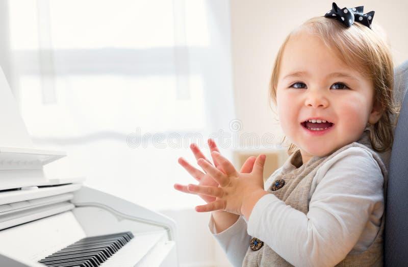 Glückliches lächelndes Kleinkindmädchen aufgeregt, um Klavier zu spielen stockfoto