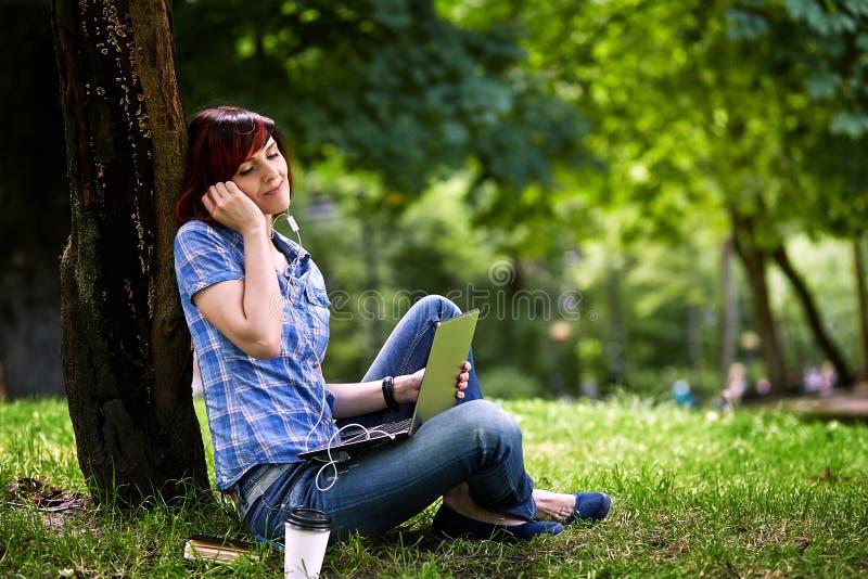 Glückliches lächelndes Mädchen, das online arbeitet stockfoto