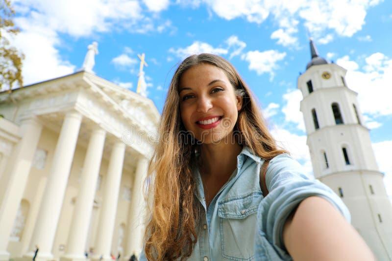 Glückliches lächelndes Mädchen, das selfie Foto vor Vilnius-Kathedrale, Litauen macht Schöne junge Frau, die in Europa reist stockbilder