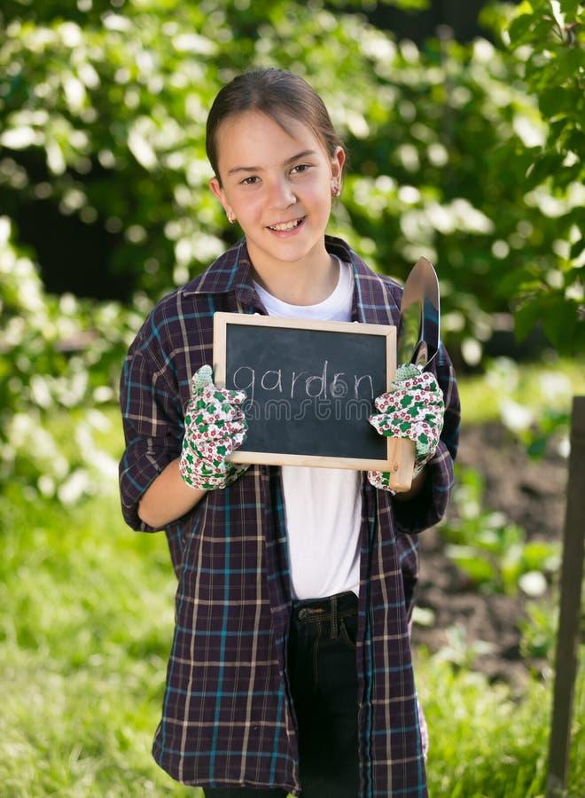 Glückliches lächelndes Mädchen, das Tafel mit Wort hält stockbilder