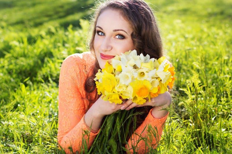 Glückliches lächelndes Mädchen mit Gelb blüht Narzissen lizenzfreies stockfoto