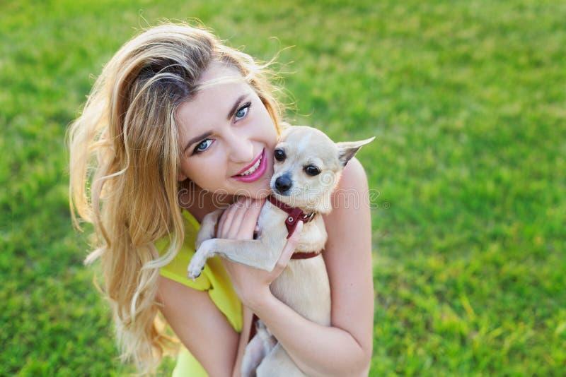 Glückliches lächelndes Mädchen oder Frau des Zaubers, die nettes Chihuahuahündchen auf grünem Rasen auf dem Sonnenuntergang halte lizenzfreie stockbilder