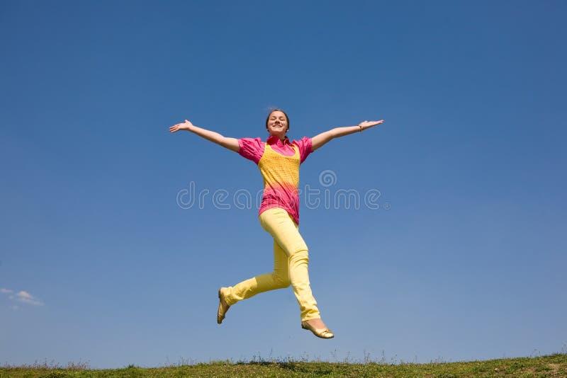 Glückliches lächelndes Mädchen - springend stockfotografie