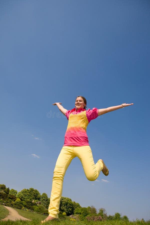 Glückliches lächelndes Mädchen - springend stockbilder