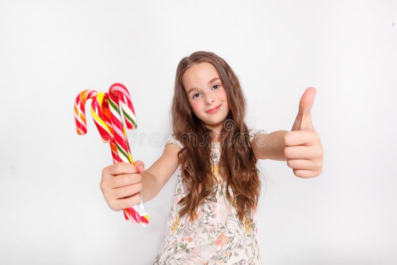 Glückliches, lächelndes nettes kleines Mädchen mit cristmas Zuckerstangen O.k. sagen Aufstellung gegen eine weiße Wand stockbild