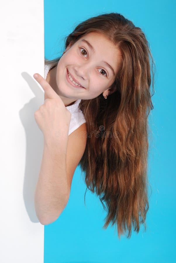 Glückliches lächelndes schönes junges Mädchen, das leeres Schild oder copyspace für Slogan oder Text zeigt stockfotos