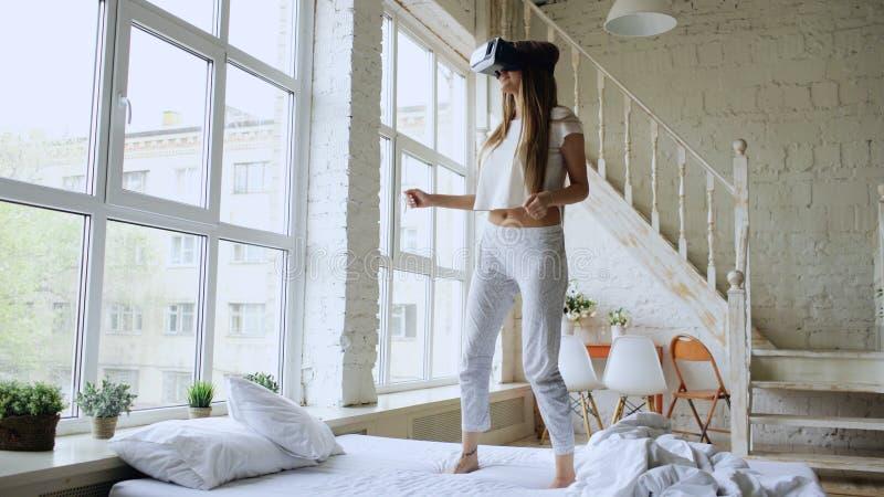 Glückliches lächelndes Tanzen der jungen Frau beim Erhalten von Erfahrung unter Verwendung 360 VR-Kopfhörergläser virtueller Real lizenzfreies stockfoto