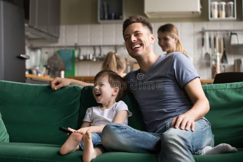 Glückliches lachendes aufpassendes Fernsehen des Vati- und Kindersohns zusammen stockfotos