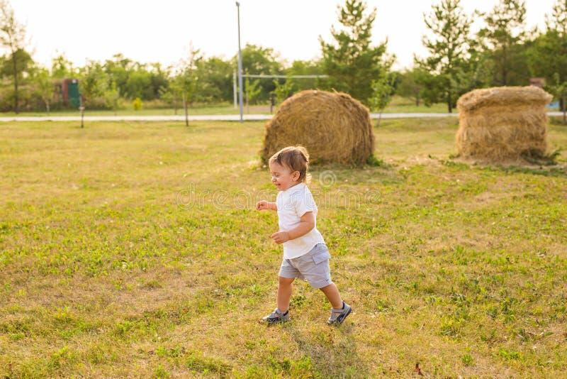 Glückliches lachendes Baby, das auf Sommer- oder Herbstfeld läuft lizenzfreie stockbilder