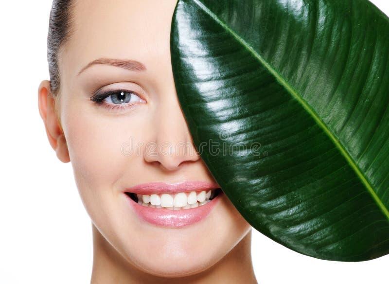 Glückliches lachendes Gesicht der Frau und des großen grünen Blattes stockfotografie