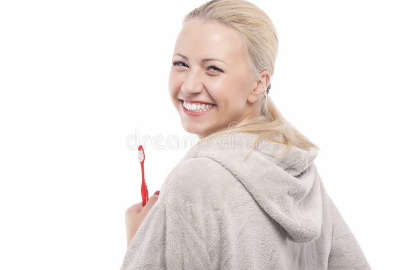 Glückliches lachendes kaukasisches blondes Mädchen, das manuelle Zahnbürste hält lizenzfreie stockfotografie