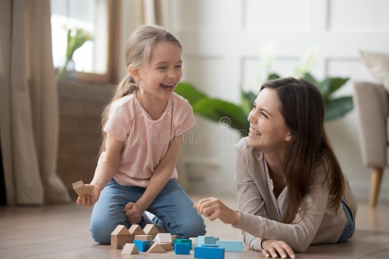 Glückliches lachendes Spielen der Mutter- und Kindertochter mit Holzklötzen lizenzfreies stockfoto
